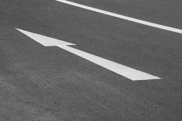 Weiße pfeilrichtung auf die asphaltstraße - transporthintergrund