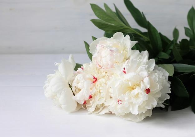 Weiße pfingstrosen auf weißem holz