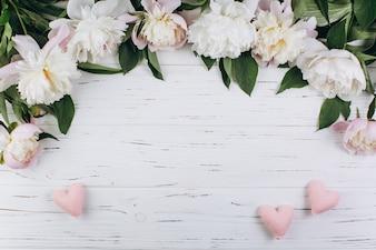 Weiße Pfingstrosen und rosa Herzen auf einem hölzernen Hintergrund. Kopieren Sie Platz und Wohnung legen.