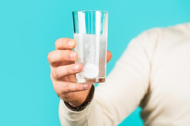 Weiße pille und ein glas wasser in menschenhänden.