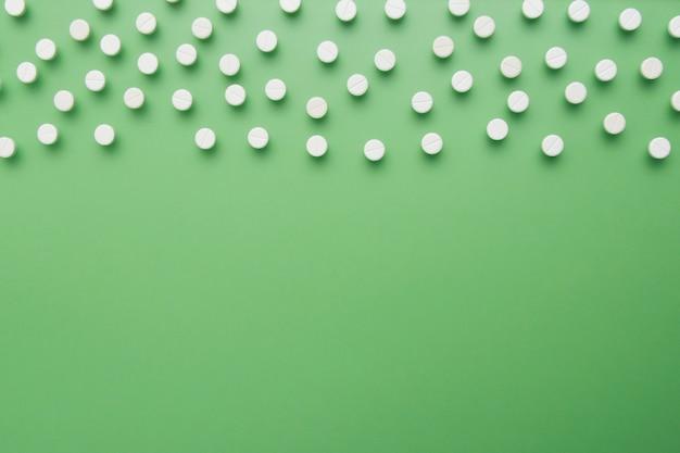 Weiße pillen auf dem grünen hintergrund getrennt. flach liegen. kopieren sie platz.
