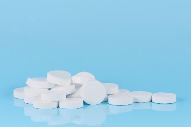 Weiße pillen auf einem blauen hintergrund. stapel der pillennahaufnahme.