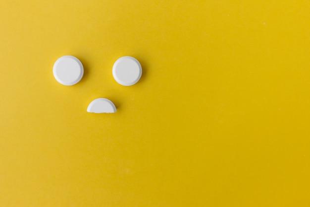 Weiße pillen auf gelb mit kopienraum in form eines smiley