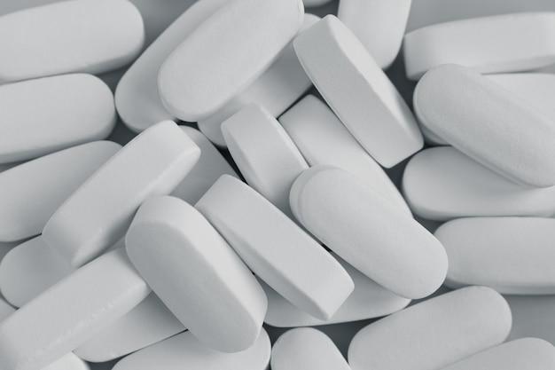 Weiße pillen auf weißem hintergrund. draufsicht
