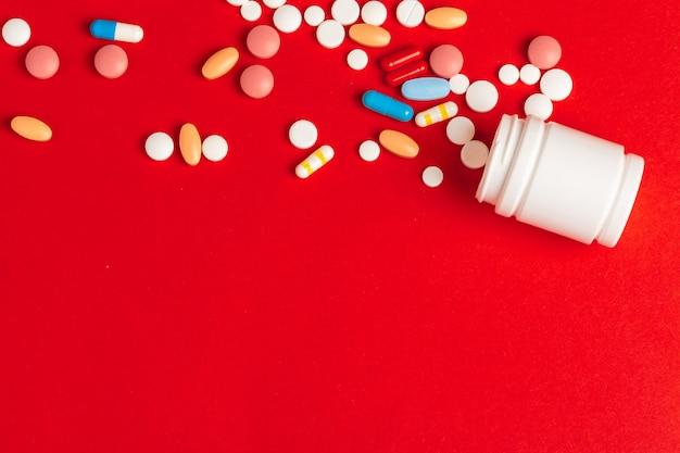 Weiße pillen, die aus einer gestürzten weißen flasche auf rotem hintergrund heraus verschüttet werden