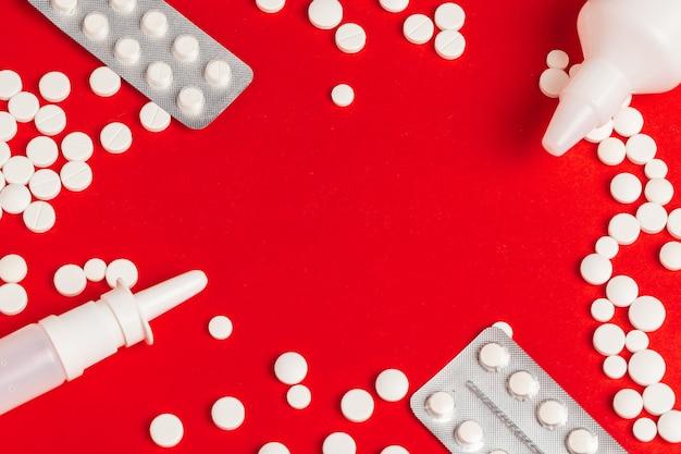 Weiße pillen, die aus einer gestürzten weißen flasche auf rotem rahmenhintergrund heraus verschüttet werden