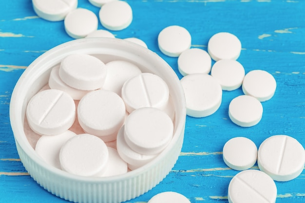 Weiße pillen wurden aus einem weißen behälter über blauem hölzernem heraus verschüttet
