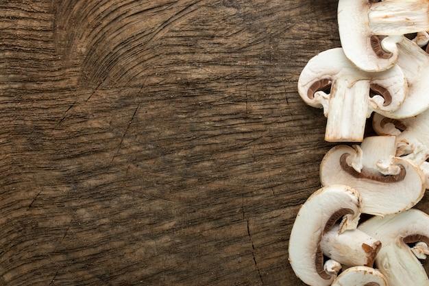 Weiße pilze frisch geschnitten auf braunem holzschreibtisch