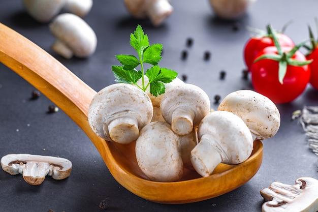 Weiße pilze im hölzernen löffel mit petersilie, dill, tomatenkirsche und frischem geschnittenem champignon auf tabelle für das kochen von selbst gemachten köstlichen tellern