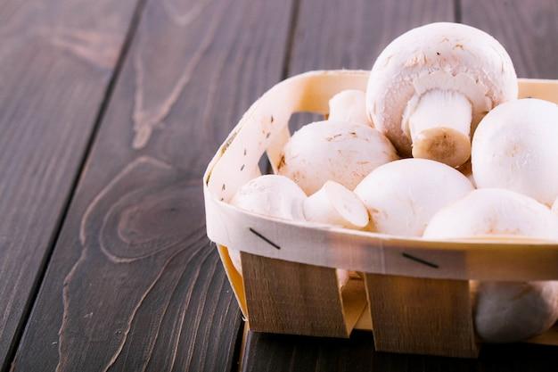 Weiße pilze liegen auf korb auf dunklem holztisch