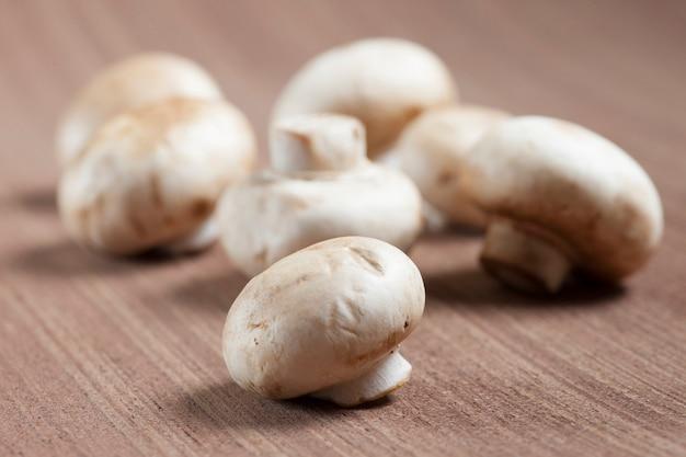 Weiße pilze über hölzernem backgroung