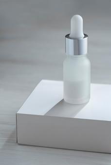 Weiße pipettenflasche auf weißer karikaturbox auf holztisch