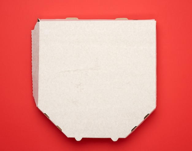 Weiße pizzaschachtel der quadratischen pappe auf rotem hintergrund