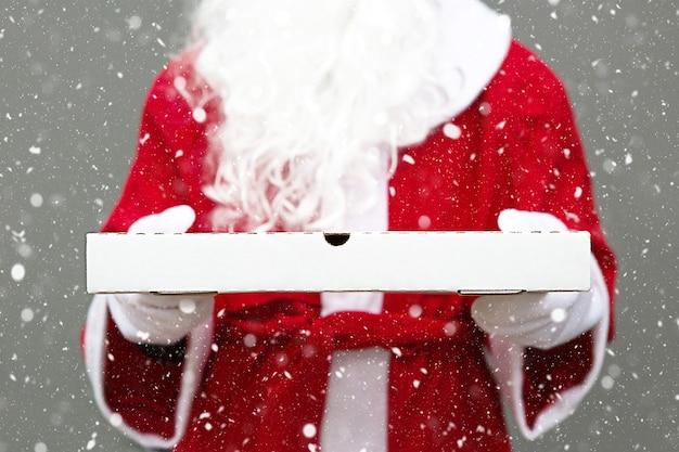 Weiße pizzaschachtel in den händen des weihnachtsmannes in weißen handschuhen, mit bart, in einem roten mantel. fast-food-lieferung zu weihnachten. silvester-aktion. arbeiten in der feiertagsgastronomie. platz kopieren, mock-up