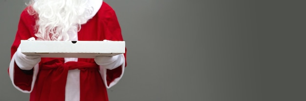 Weiße pizzaschachtel in den händen des weihnachtsmannes in weißen handschuhen.