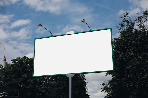 Weiße plakatwand auf grünen blättern