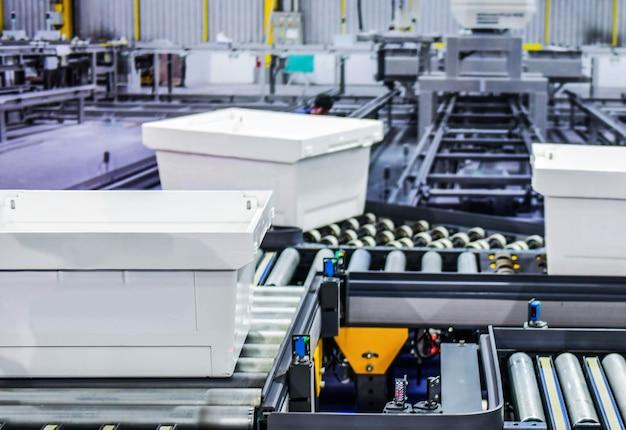 Weiße plastikboxen auf förderband. pakettransportsystemkonzept