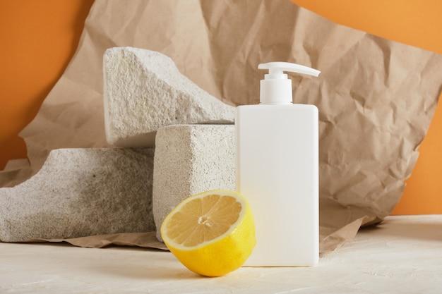 Weiße plastikflasche mit spender für seifen-ioi-creme, zitronen- und betonpodien, brauner hintergrund