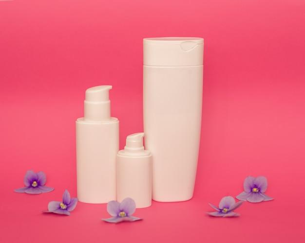 Weiße plastikflaschen auf einem rosa hintergrund, ein satz kosmetikbehälter mit einem spender. kopierplatz, leerer platz für text. toilettenartikel, pumpenlotion. feuchtigkeitscreme für körper und gesicht.