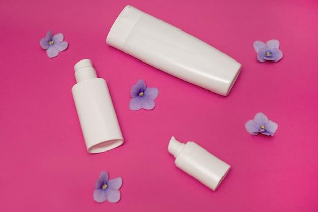 Weiße plastikflaschen auf rosa hintergrund, satz kosmetikbehälter mit spender. kopierplatz, leerer platz für text. toilettenartikel, pumpenlotion. feuchtigkeitscreme für körper, gesicht. konzept der hautpflege