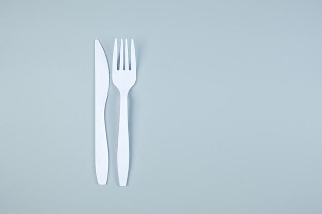 Weiße plastikgabel und messer auf grau mit kopierraum für text. umweltschutz, null abfall, wiederverwendbar, sag nein plastik, weltumwelttag und tag der erde konzept