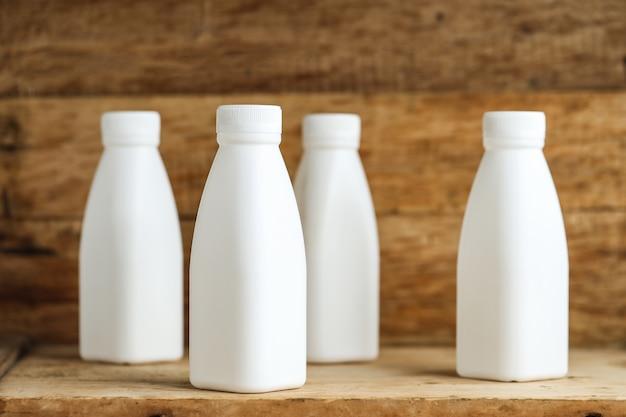 Weiße plastikmilchflaschen auf retro holztischhintergrund