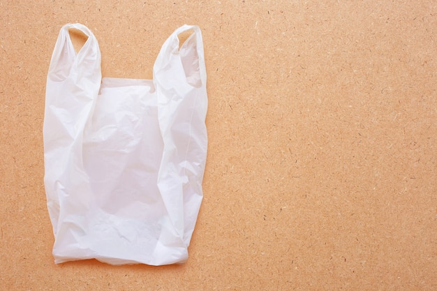 Weiße plastiktasche auf hölzernem hintergrund.