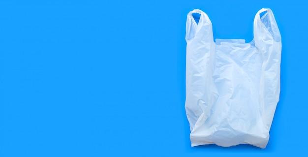Weiße plastiktüte auf blauem tisch.