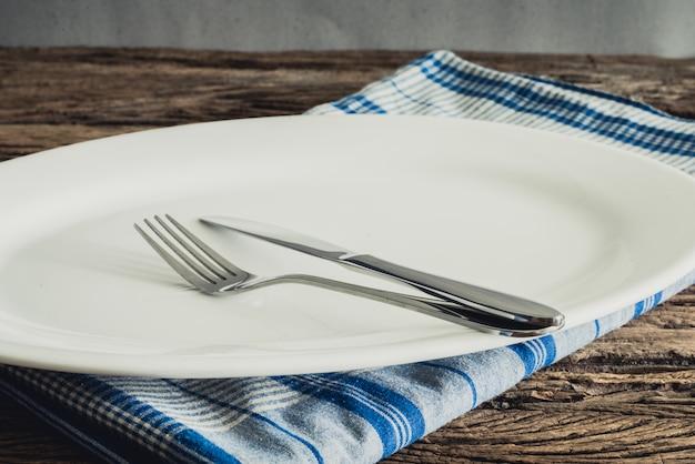 Weiße platte auf einer servietten- und silbergabel