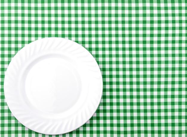 Weiße platte auf grünem und weißem kariertem gewebetischdecken-hintergrund.