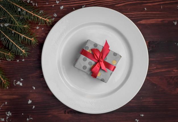 Weiße platte mit einem geschenk eingewickelt, draufsicht