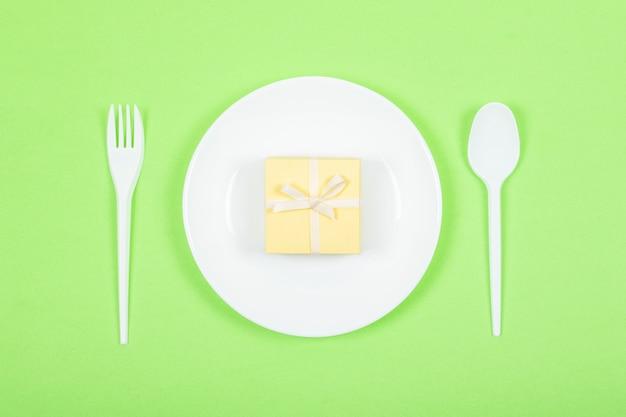 Weiße platte mit gelber geschenkbox