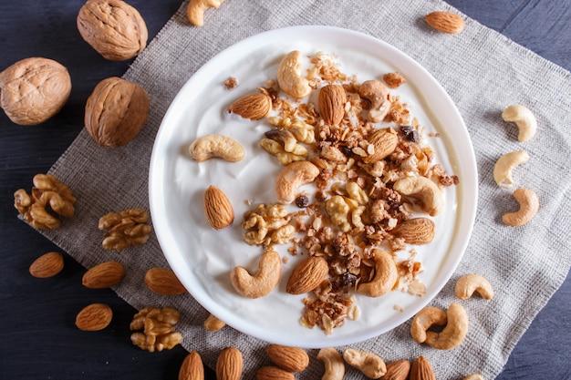 Weiße platte mit griechischem joghurt, granola, mandel, acajoubaum, walnüssen
