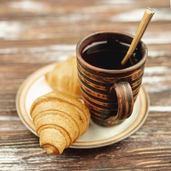 Weiße platte mit hörnchen und kaffeetasse