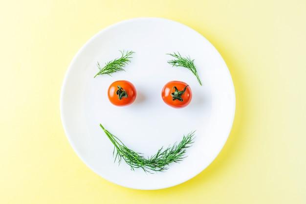 Weiße platte mit kleinen tomaten und dill.