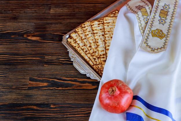 Weiße platte mit matzah oder matza und passahfest haggadah auf einem weinleseholz