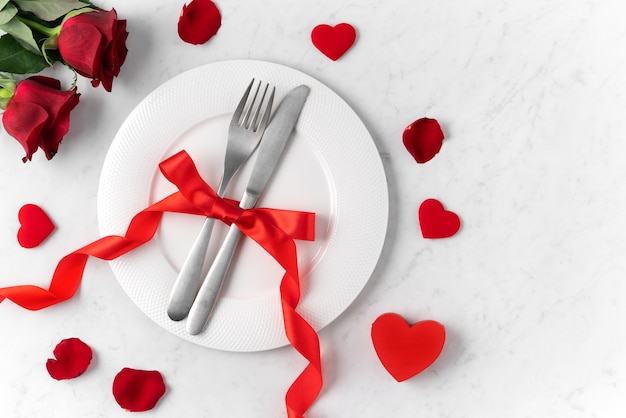 Weiße platte mit roter rosenblume auf weißem marmor-tischhintergrund für valentinstag-datierungsfeiertagsmahlzeitkonzept.
