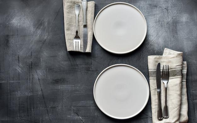 Weiße platte, tischbesteck und serviette auf dunkler steintabelle. sitzordnung bei tisch