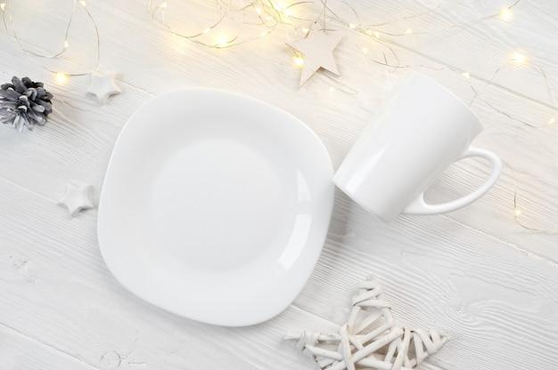 Weiße platte und becher des modells auf einem weihnachtsweißen hölzern