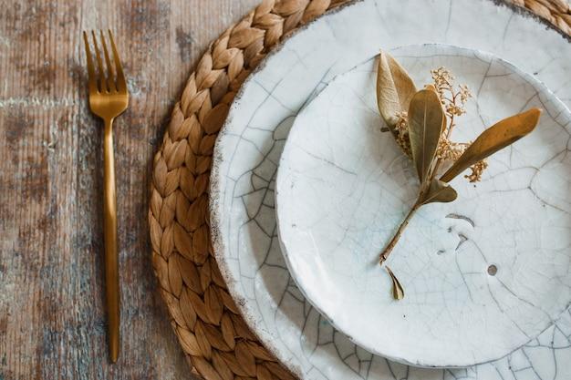 Weiße platte und goldene gabel mit einem löffel, geräte für das braten, hochzeitsdekoration.
