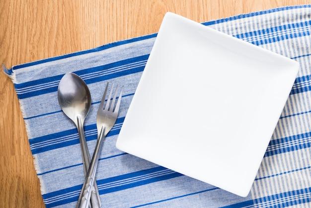 Weiße platte und silberner löffel und gabel