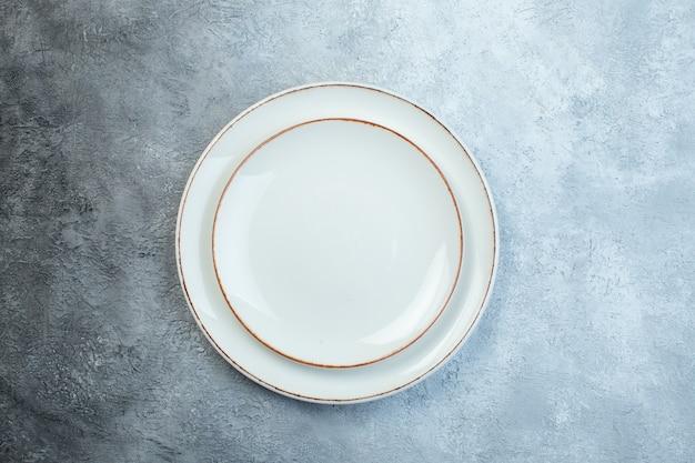 Weiße platten auf halbdunkler hellgrauer oberfläche mit gealterter grobkörniger verlaufsoberfläche