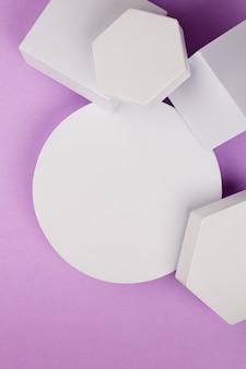 Weiße plattform mit geometrischen formen auf violettem hintergrund