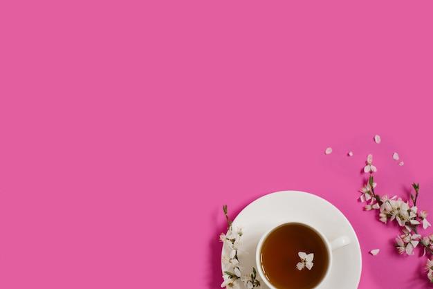 Weiße porzellantasse mit schwarzem tee. zweige eines blühenden apfelbaums liegen auf einem leuchtend rosa hintergrund. frühlingskonzept. platz kopieren
