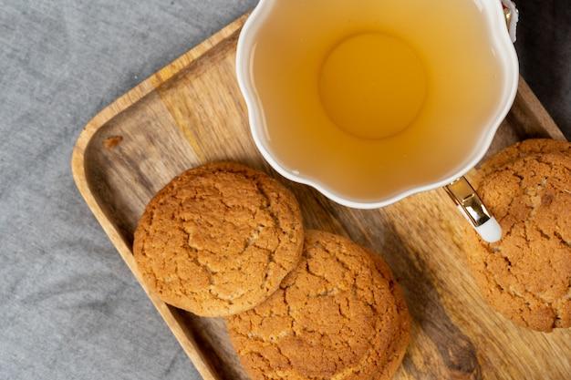 Weiße porzellantasse tee und haferkekse auf einem tisch