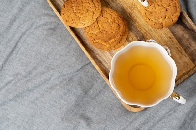Weiße porzellantasse tee und haferplätzchen auf einer tabelle