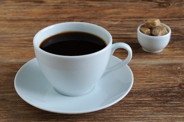 Weiße porzellantasse und untertasse mit schwarzem kaffee und braunem zuckerrohr auf holztisch