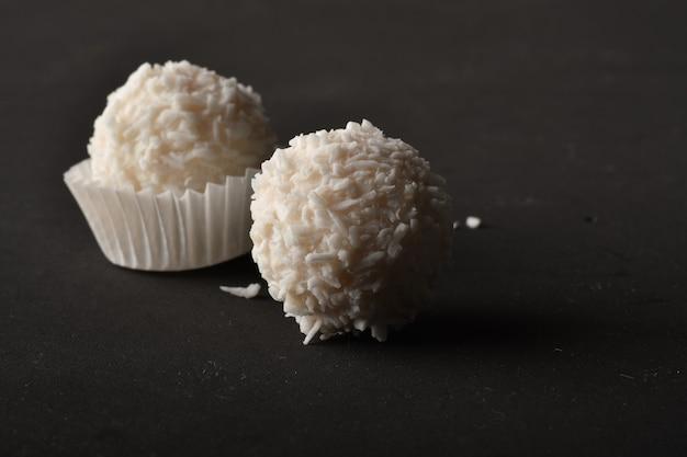 Weiße praline mit kokos-topping auf schwarzem hintergrund