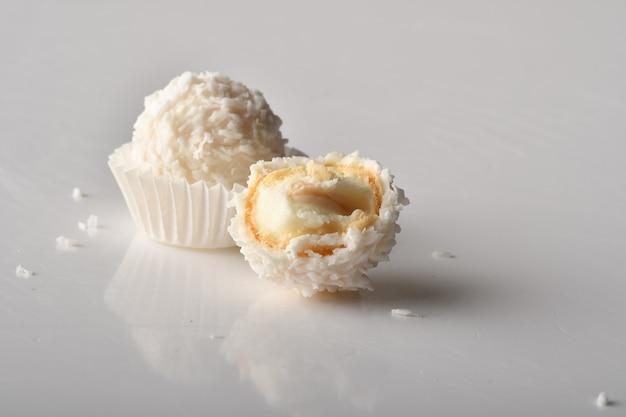 Weiße praline mit kokos-topping auf weißem hintergrund