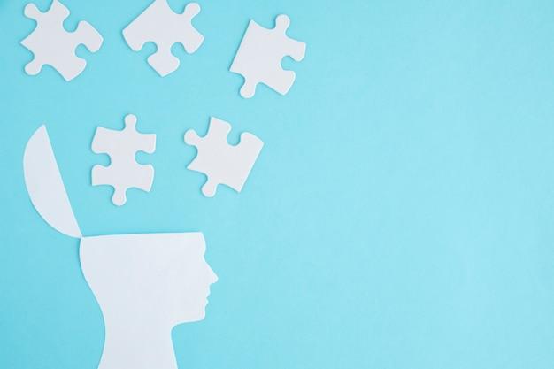 Weiße puzzlespiele über dem offenen kopf auf blauem hintergrund